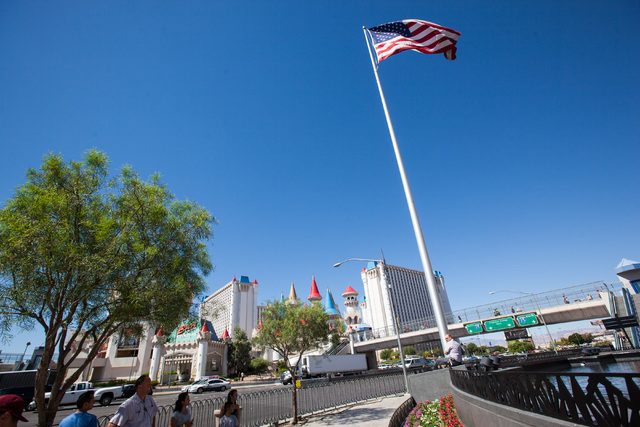 Engineer Randy, last name declined, lower right, prepares to lower the flag to half-staff in honor of Kirk Kerkorian, one of the founders of modern Las Vegas, outside of the New York-New York hote ...