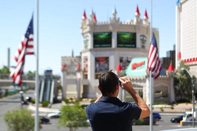 A man takes a photo of flags at half-staff in honor of Kirk Kerkorian, one of the founders of modern Las Vegas, outside of the New York-New York hotel-casino in Las Vegas on Tuesday, June 16, 2015 ...
