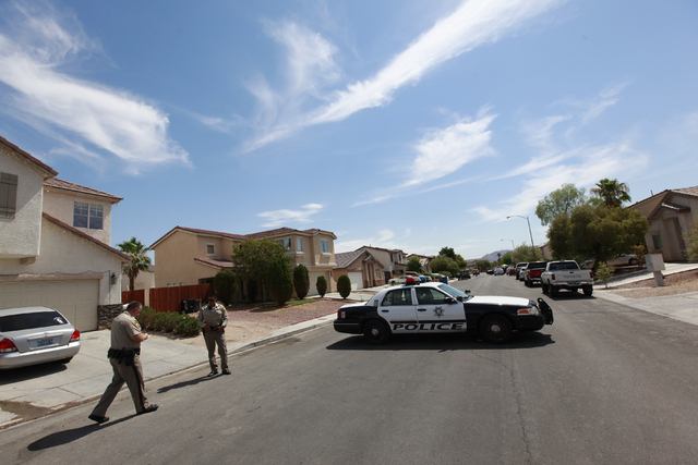 Las Vegas police investigate the scene of a shooting that left one person dead on the 3800 block of King Palm Avenue, near Alexander and Pecos roads, in Las Vegas on Tuesday, June 30, 2015. Anothe ...