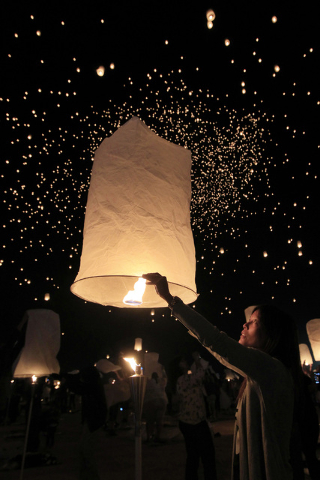 Tess Brown, from San Diego, prepares her paper lantern for flight at the RiSE Festival Saturday, Oct. 18, 2014 on a dry lake bed near Jean.  (Sam Morris/Las Vegas Review-Journal)