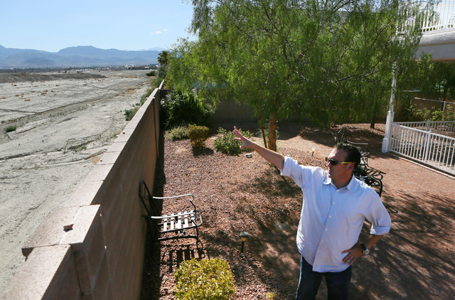 Steven Berkabile gestures towards an open parcel of land behind the wall in his backyard Wednesday, May 27, 2015, in Las Vegas. Shiron Development LLC proposed a three-story and 261-unit apartment ...