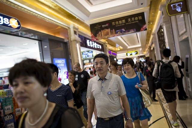 Tourists walk inside a shopping mall at Galaxy Macau resort in Macau, China, on Wednesday, May 27, 2015. As revenue plummets at China's only legal gambling hub, global casino operators have a new  ...