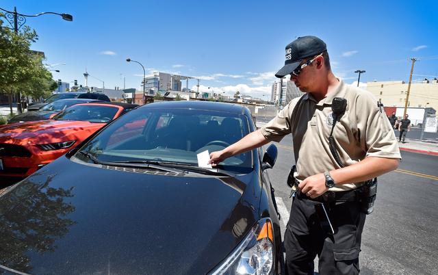 Parking enforcement officer Joshua Kuykendall issues a parking citation to a vehicle along Seventh Street in downtown Las Vegas on Friday, June 12, 2015. (David Becker/Las Vegas Review-Journal)