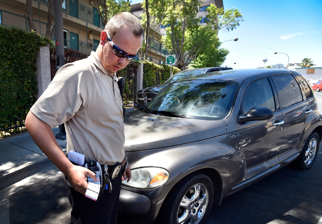 Parking enforcement officer Joshua Kuykendall prints a warning citation for no current registration sticker visible on a vehicle along 7th Street in downtown Las Vegas on Friday, June 12, 2015. Ku ...