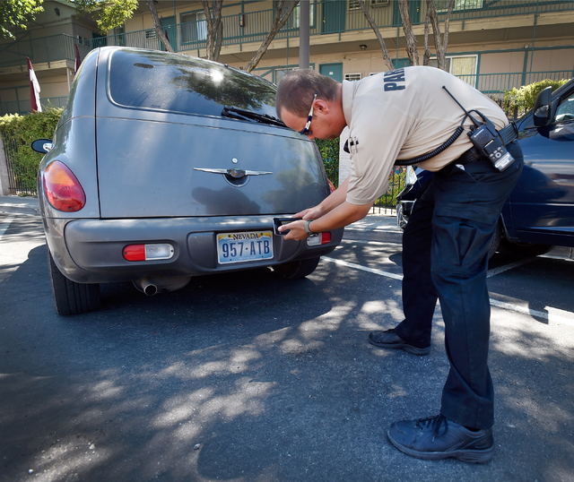 Parking enforcement officer Joshua Kuykendall photographs a license plate before issuing a warning citation for no current registration sticker visible on a vehicle along 7th Street in downtown La ...