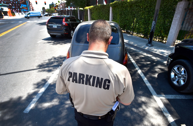 Parking enforcement officer Joshua Kuykendall writes a warning citation for no current registration sticker visible on a vehicle along 7th Street in downtown Las Vegas on Friday, June 12, 2015. Ku ...
