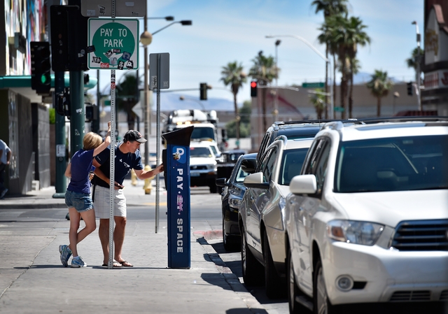 Motorists pay at a parking meter along 6th Street in downtown Las Vegas on Friday, June 12, 2015. (David Becker/Las Vegas Review-Journal)