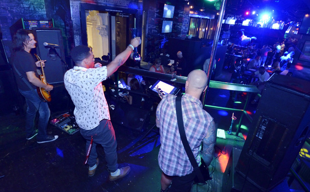 "Kyle Churche (cq), center, sings a cover version of OutKast's ""Hey Ya"" with house band members Jimmy Oleson (cq), left, and Tony Santoro during Rockstar Karaoke in the Rockhouse at the P ..."