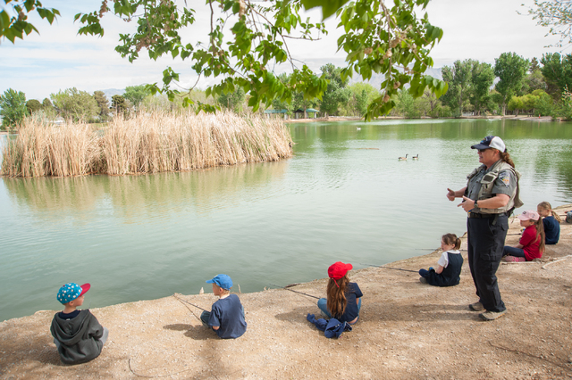 Conservation Educator Ivy Santee, right, of the Nevada Department of Wildlife, instructs first grade students from Pinecrest Academy in Henderson, Nev., how to fish at Floyd Lamb Park at Tule Spri ...