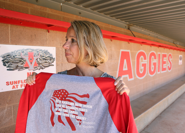 Arbor View High School Assistant Principal Denise Tomchek holds up a baseball shirt honoring her friend and colleague former principal Pat Hayden while standing in the Pat Hayden Field dugout at A ...