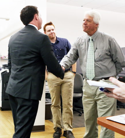 Jason Taylor, left, newly named President and Publisher of the Review-Journal and President of GateHouse Media's Western U.S. Publishing Operations, shakes hands with Keith Rogers in the newsroom  ...