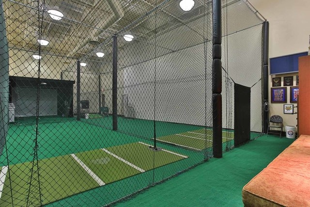 Courtesy photo  The Spring Valley home's recreation center also includes an indoor batting cage and golf simulator.