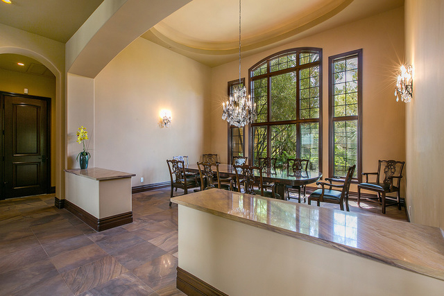 Courtesy photo The airy formal dining room is notable for its ornate chandelier and its window view of the verdant, sheltering property outside.