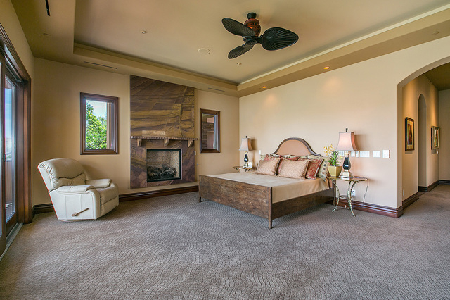 The home has four, suite-style private quarters. This is the master upstairs bedroom, which has patio access. It and a fireplace. (Courtesy photo)