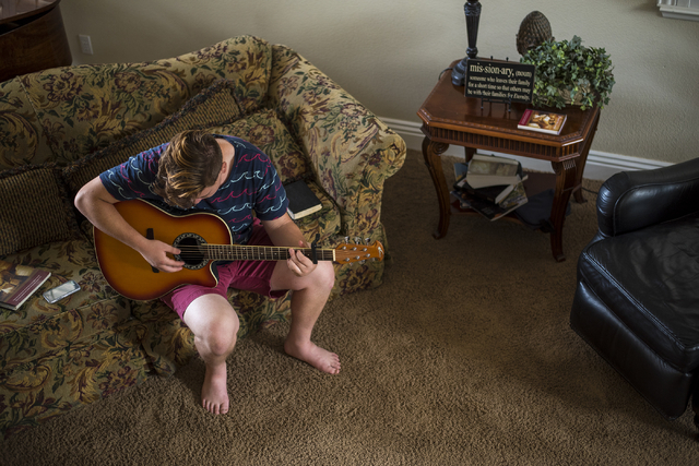 Cole Ballard, 18, plays guitar to relax between studying for his two-year mission trip to Chile at his home in Henderson on Wednesday, May 13, 2015. (Joshua Dahl/Las Vegas Review-Journal)
