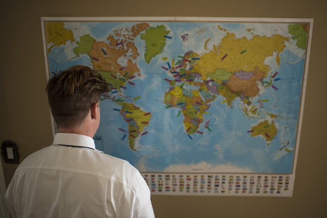 Cole Ballard, 18, looks at a map with guesses by friends and family of where his mission trip might be at his home in Henderson on Wednesday, May 13, 2015. Cole is going on a two-year mission trip ...