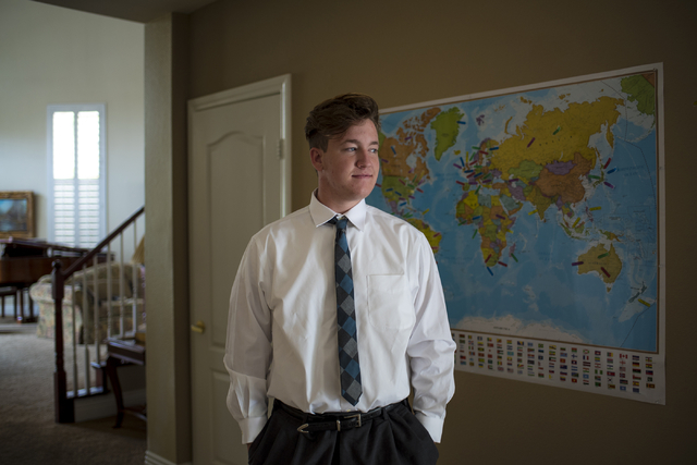 Cole Ballard, 18, stands in front of a map with guesses by friends and family of where his mission trip might be at his home in Henderson on Wednesday, May 13, 2015. Cole is going on a two-year mi ...