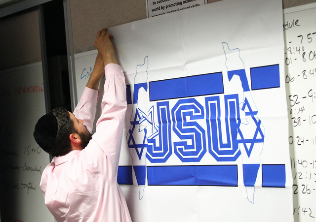 Rabbi Yahuda Maryles sets up a banner for the Jewish Student Union meeting at Advanced Technologies Academy in Las Vegas on Friday, May 9, 2014. (Chase Stevens/Las Vegas Review-Journal)