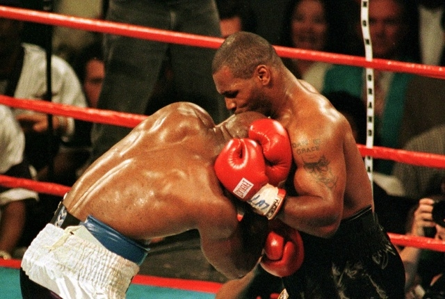Mike Tyson bites the ear of Evander Holyfield during the third round of the WBA Heavyweight Championship fight in Las Vegas, June 28. The fight was called after Tyson was disqualified. (File photo)