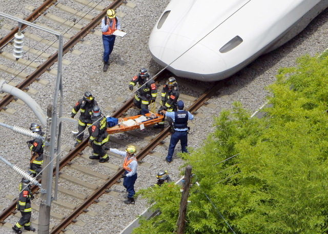 A passenger on the stretcher is carried by rescue workers from a Shinkansen bullet train after it made an emergency stop in Odawara, south of Tokyo, in this aerial view photo taken by Kyodo June 3 ...