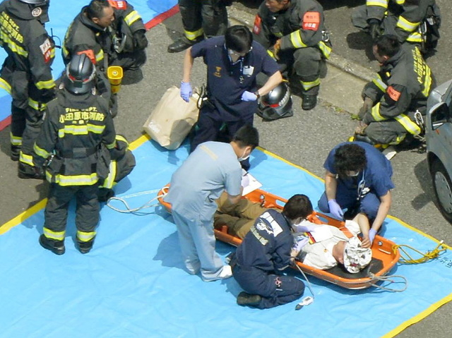 A passenger receives medical treatment from rescue workers after their Shinkansen bullet train made an emergency stop in Odawara, south of Tokyo, in this aerial view photo taken by Kyodo June 30,  ...
