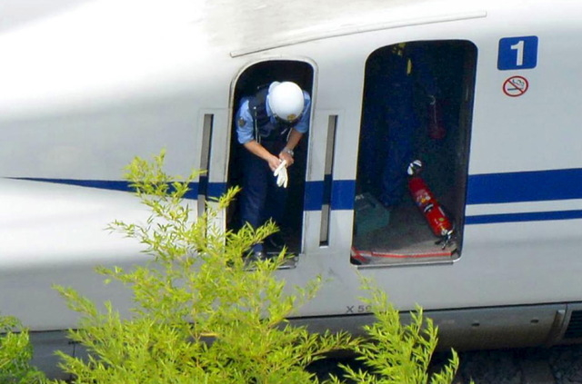 An extinguisher (R) is seen as a police officer investigates a Shinkansen bullet train after it made an emergency stop in Odawara, south of Tokyo, in this aerial view photo taken by Kyodo June 30, ...