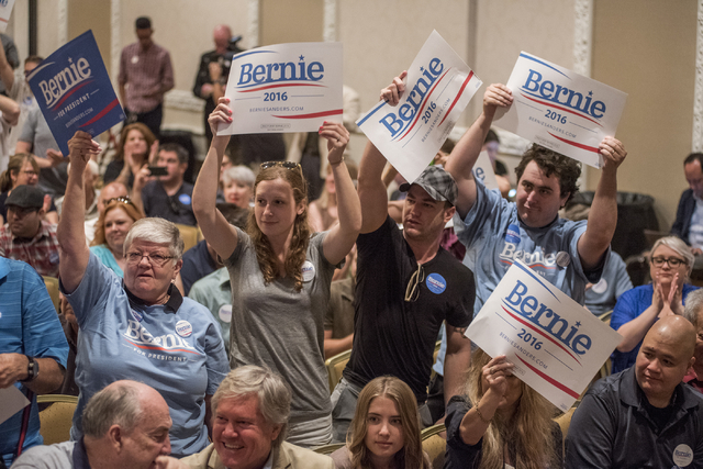 Supporters hold up signs for U.S. Sen. Bernie Sanders as he speaks at Treasure Island hotel-casino in Las Vegas on Friday, June 19, 2015. Senator Sanders is an independent from Vermont who is seek ...