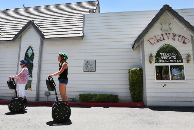 Carlyne Meyer, left, and her granddaughter Katie Smith, both of Springfield, Ill., pause on their Segways near A Special Memory wedding chapel drive-up window during a group tour of downtown with  ...
