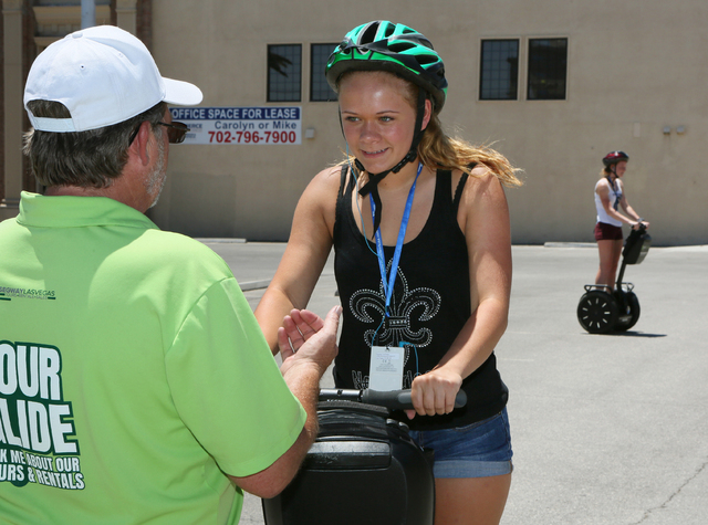Guide Scott Milheiser, from left, teaches Katie Smith, of Springfield, Ill., how to ride a Segway as Ashley Smith practices in an empty lot before the group participates in an hour tour of downtow ...