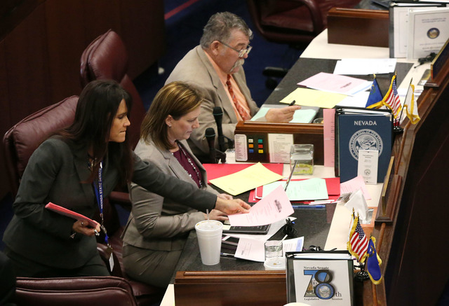 Nevada Senate Assistant Sgt.-at-Arms Teri Peterson hands out paperwork to Senate Republicans Becky Harris and Pete Goicoechea during the final hours of the session at the Legislative Building in C ...