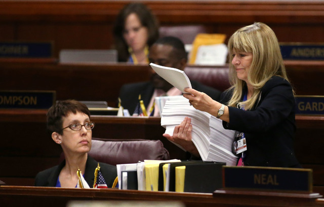 Nevada Assemblywoman Heidi Swank, D-Las Vegas, gets paperwork from Assistant Sgt.-at-Arms Vickie Kieffer during Assembly floor action in the final hours of the session at the Legislative Building  ...