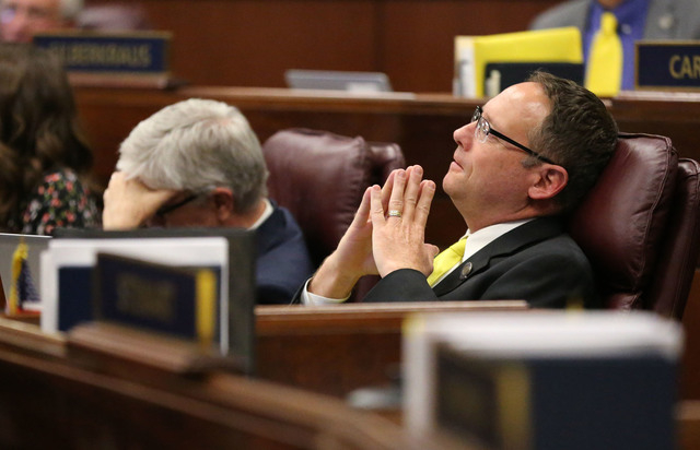 Nevada Assemblymen Erven Nelson, R-Las Vegas, left, and Mike Sprinkle, D-Sparks watch as the final chaotic minutes of the session tick down at the Legislative Building in Carson City, Nev., on Mon ...
