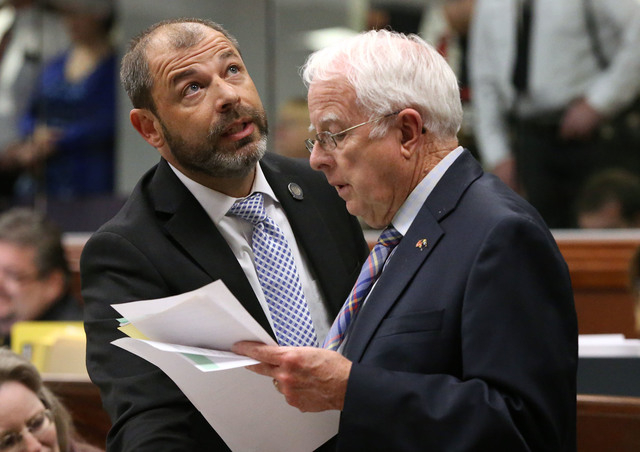 Nevada Assembly Republicans Paul Anderson, left, and Lynn Stewart work on the Assembly floor as the final chaotic minutes of the session tick down at the Legislative Building in Carson City, Nev., ...