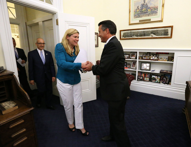 Nevada Sens. Mark Lipparelli, Mo Denis and Patricia Farley tell Gov. Brian Sandoval they concluded their business following the end of the session at the Legislative Building in Carson City, Nev., ...