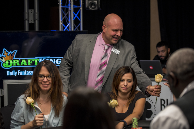Charlie Ciresi, lead tournament supervisor, passes roses out during the final table of the Ladies Championship at the World Series of Poker at the Rio Hotel Convention Center in Las Vegas on Sunda ...