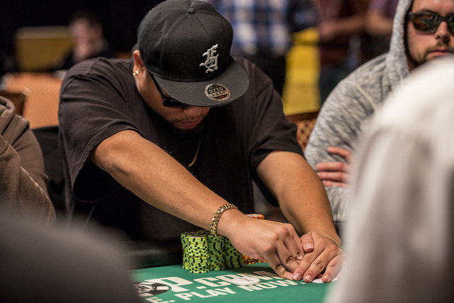 """Christian Rodriguez checks his cards during the World Series of Poker's $1,500 buy-in """"Monster Stack"""" tournament held at the Rio Convention Center in Las Vegas on Tuesday, June 16, 2015. ..."""