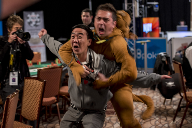 """Fernando Konishi celebrates with a fan dressed as Scooby Doo after knocking Jeff Kaplan out of the tournament during the World Series of Poker's $1,500 buy-in """"Monster Stack"""" tournament  ..."""