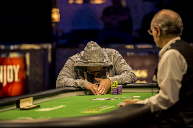 """Eric Place checks his cards during the final table of the World Series of Poker's $1,500 buy-in """"Monster Stack"""" tournament held at the Rio Convention Center in Las Vegas on Wednesday, Ju ..."""