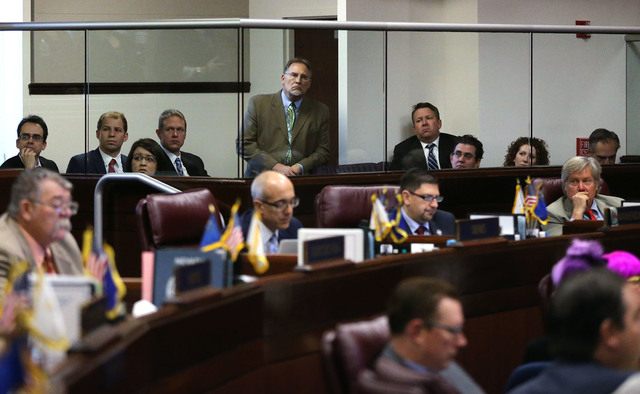 Representatives from Gov. Brian Sandoval's office listen to Senate floor discussion on the governor's $1.1 billion general fund tax package from the Senate gallery at the Legislative Building in C ...