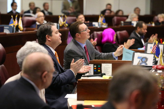 Nevada Senate Majority Leader Michael Roberson, R-Henderson, center, applauds as a record $1.1 billion general fund tax package receives passage on the Senate floor at the Legislative Building in  ...