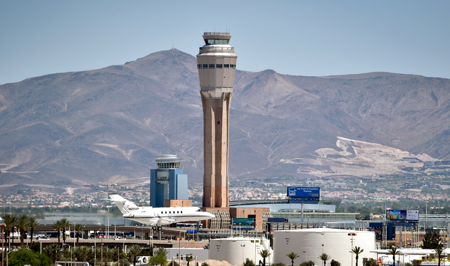 A private jet prepares to land at McCarran International Airport under the shadow of a still under construction air traffic control tower on Monday, June 8, 2015. The new 352-foot tower originally ...