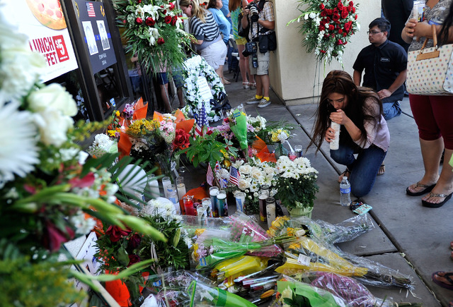 People gather around a makeshift memorial created at CiCi's Pizza, 309 N. Nellis Blvd., on June 9, 2014.  Las Vegas police officers Alyn Beck and Igor Soldo were shot and killed on June 8 as they  ...