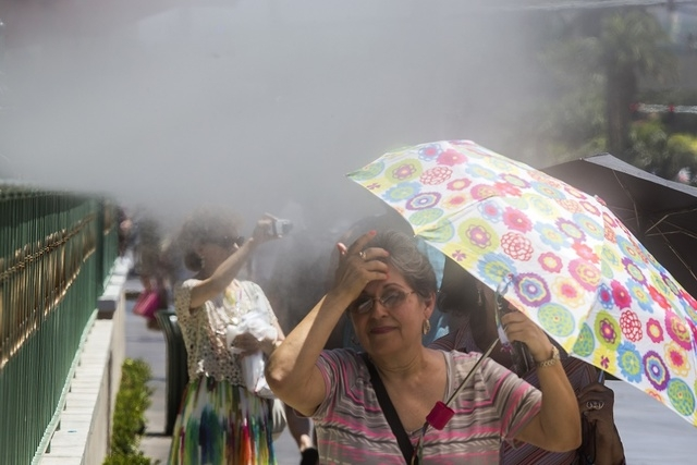 A woman wipes her face at row misters in front of the Sugar Factory on Tuesday, July 1, 2014. The temperatures will range from 106-111 over the next few days.(Jeff Scheid/Las Vegas Review-Journal)
