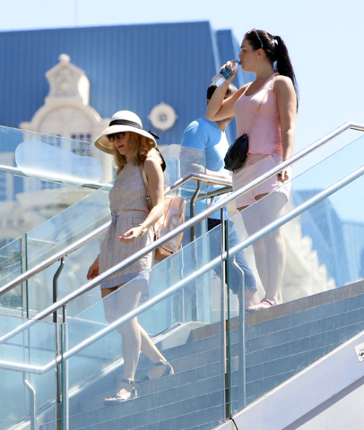 Tourists wearing hat and drinking water walk down stairs near The Cosmopolitan hotel-casino on Las Vegas Blvd., on Friday, June 19, 2015. High temperatures are expected to stay hotter than normal  ...