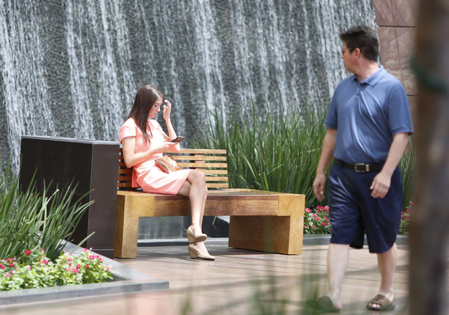 A woman sits as checks her phone near a waterfall in the Aria's hotel-casino north lobby on Las Vegas Blvd., on Friday, June 19, 2015. High temperatures are expected to stay hotter than normal for ...