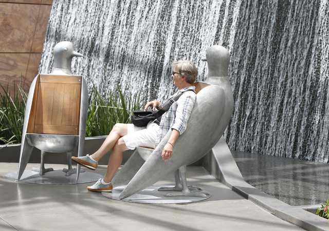A woman sits on a stainless steel bird chair near a waterfall in the Aria's hotel-casino north lobby on Las Vegas Blvd., on Friday, June 19, 2015. High temperatures are expected to stay hotter tha ...