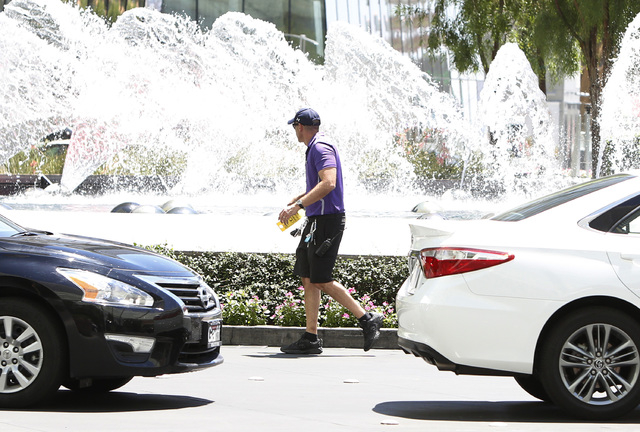 A valet parking attendant runs past the fountain at the Aria hotel-casino on Las Vegas Blvd. near Harmon Ave., on Friday, June 19, 2015. High temperatures are expected to stay hotter than normal f ...