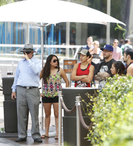 Tourists shelter under umbrella as they wait for a taxi at the Aria hotel-casino on Las Vegas Blvd. near Harmon Ave., on Friday, June 19, 2015. High temperatures are expected to stay hotter than n ...