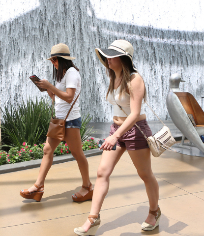 Tourists walk past a waterfall in the Aria's hotel-casino north lobby on Las Vegas Blvd., on Friday, June 19, 2015. High temperatures are expected to stay hotter than normal for the Las Vegas Vall ...