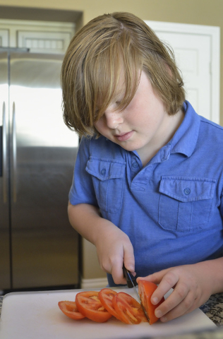 Nine-year-old Jack Newkirk slices a tomato at his home in Henderson on Wednesday, June 24, 2015. He is Nevada's winner in Michelle Obama's Healthy Lunchtime Challenge and will attend a Kids' State ...
